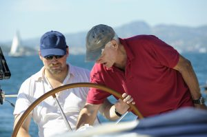 Senior Sailing Instructor Giving Advice Aboard Yacht