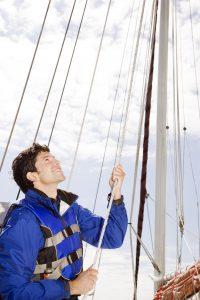 Man Hoisting Sail on Sailboat